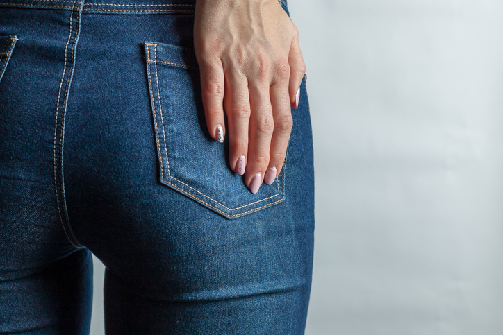 young woman behind in denim jeans. holds her hand at back pocket. hard light. concept beauty and healthy lifestyle. copy space