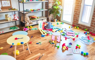 Beautiful toddler sitting on the floor playing with building blocks toy at kindergarten