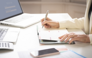 Close-up of businesswoman's hand while making note on the notebook