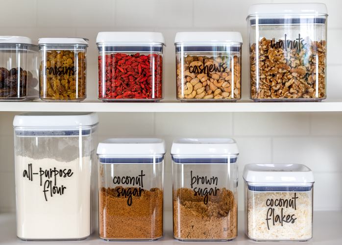 Labeled canisters in kitchen pantry